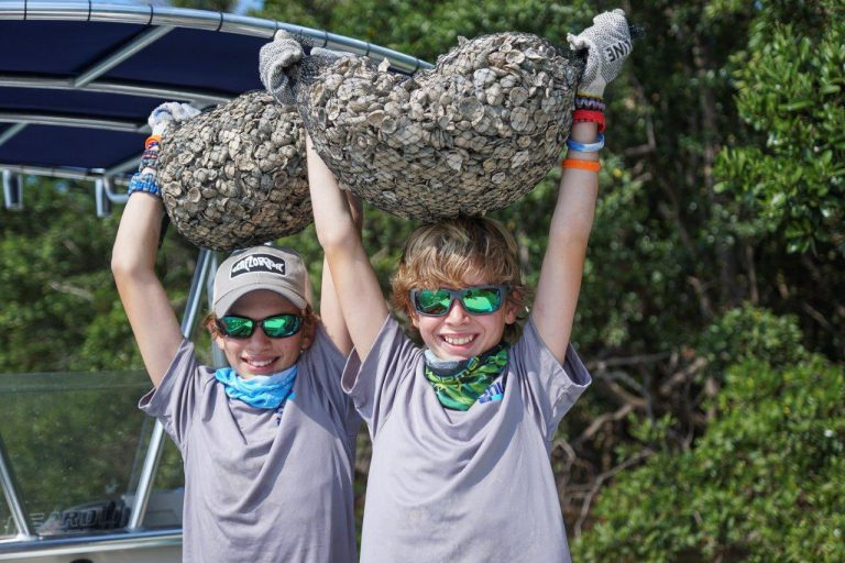 image: kids holding oyster bags